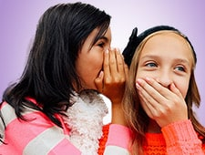 One girl whispering to another girl to her ear.